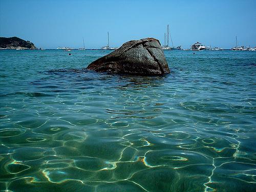 Una roca negra frente a la playa domina la Cala La Fosca